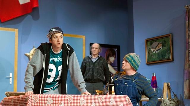 Zwei Jugendliche am Küchentisch, im Hintergrund ein älterer Mann.