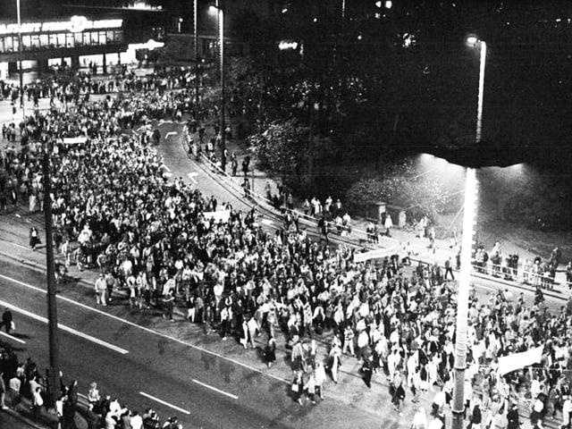 Blick auf Demonstranten in Berlin – bei Nacht.