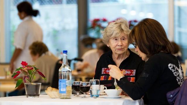 Eine Frau und eine ältere Dame sitzen an einem Tisch.