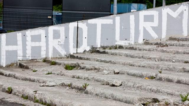 """Überreste der Stadiontreppe, dahinter auf eine Wand gesprayter Schriftzug """"Hardturm"""""""