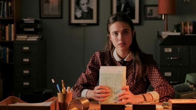 Eine junge Frau sitzt mit einem Bündel Notizen in den Händen an einem Pult.