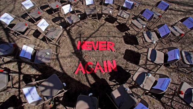 """Ein Plenum mit leeren Stühlen und der Aufschrift """"Never Again""""."""