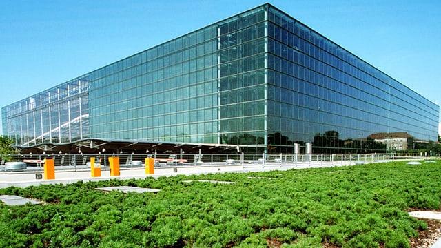 Ein riesiger rechteckiger Glasbau, im Vordergrund eine Grünfläche.