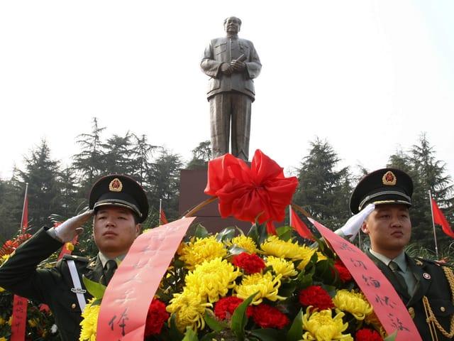Eine Statue von Mao, im Vordergrund zwei Soldaten.