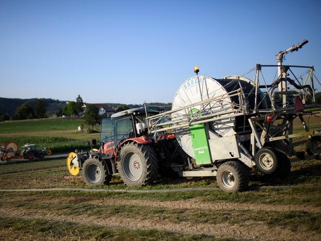Ein Traktor fährt auf einer trockenen Landwirtschaftswiese