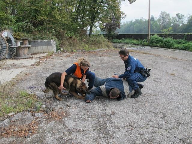 Polizist und Hundeführerin halten Mann zusammen mit Hund in Schach.