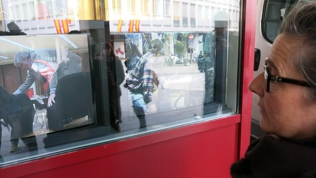 Eine Frau schaut auf zwei Fernsehbildschirme in einem Schaufenster.
