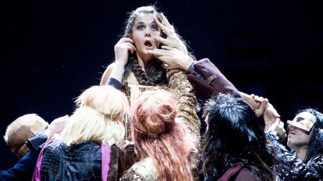 Eine Opernsängerin auf der Bühne, umringt von Leuten, die ihre Hände in ihr Gesicht halten.