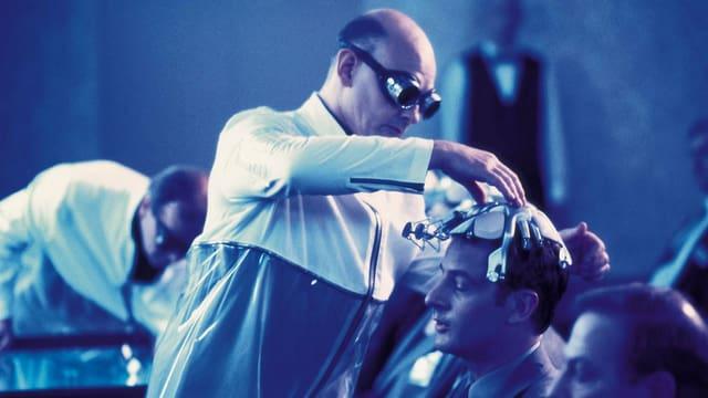 Ein Mann in weissem Kittel setzt einem anderen eine Metallkonstruktion auf den Kopf.