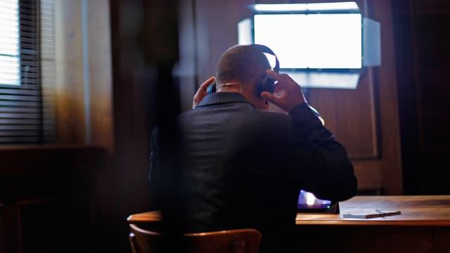 Ein Mann setzt sich einen Kopfhörer auf