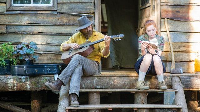 Filmstill: Ein Mann spielt Gitarre, ein Mädchen liest ein Buch.