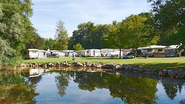 Wohnwagen und Zelte an einem Seeufer.
