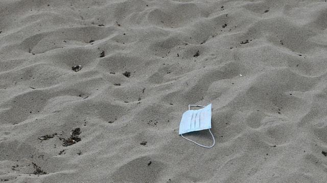 Eine Gesichtsmaske liegt im Sand am Strand von Playa de Palma auf Mallorca.
