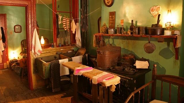 Alte Wohnungseinrichtung mit Holzofen und Wäscheleinen, durch Zimmer gespannt