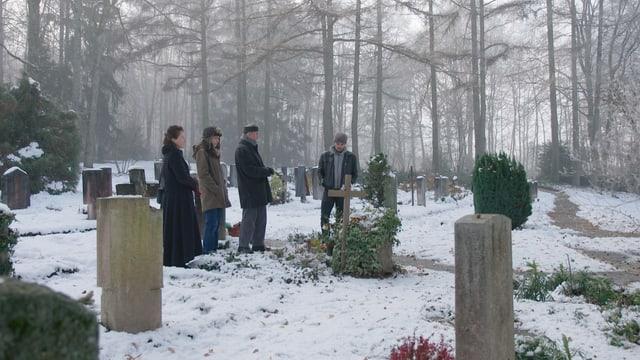 Trauernde an einem Grab.