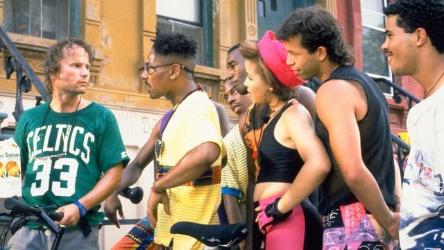 Filmszene: Ein weisser Mann im Gespräch mit einer Gruppe afroamerikanischer Männer und Frauen.