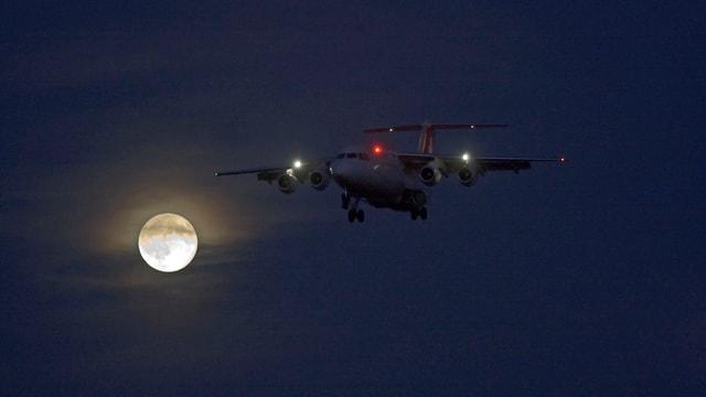 Die Lichter eines Flugzeugs in der Luft, im Hintergrund Vollmond.