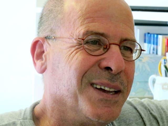 Ein Mann mittleren alters mit Brille und kurzgeschorenem Haar.