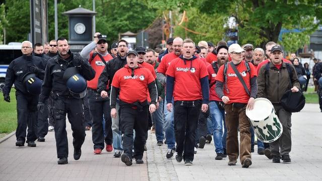 Ein Gruppe von rechtsextremen Demonstranten mit roten T-Shirts.