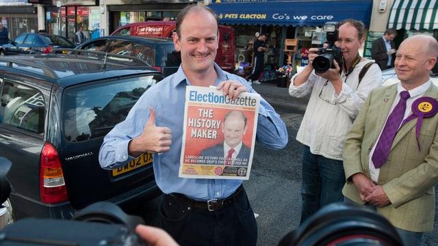 Douglas Carswell hält eine Zeitung in der Hand und streckt den Daumen hoch
