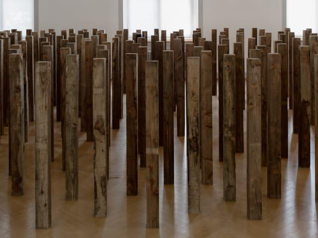 Mehrere Dutzend Holzstäbe sind in einem leeren Raum aufgereiht.