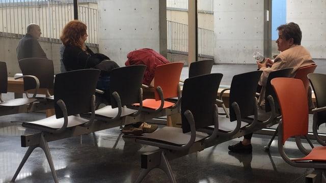 Das Wartezimmer des Hospital del Mar in Barcelona. Man sieht zwei Frauen und einen älteren Herrn, die auf orangenen Stühlen warten. Ansonsten wirkt der Raum leer und kalt.