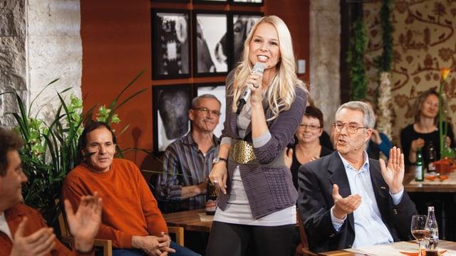 Linda Fäh mit singt umgeben von Menschen