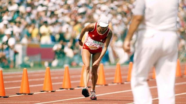Taumelnde Läuferin auf dem Weg ins Ziel.