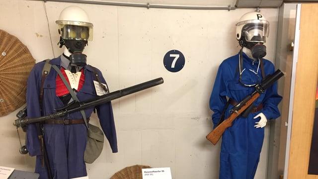 Zwei Polizeipuppen mit ältlich wirkenden, blauen Unifromen sind ausgestellt in einem Museum.