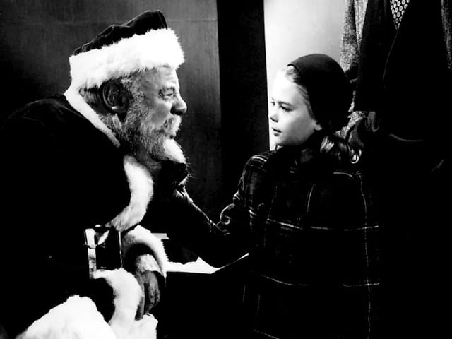 Weihnachtsmann und kleines Mädchen sehen sich an. Bild in schwarzweiss.