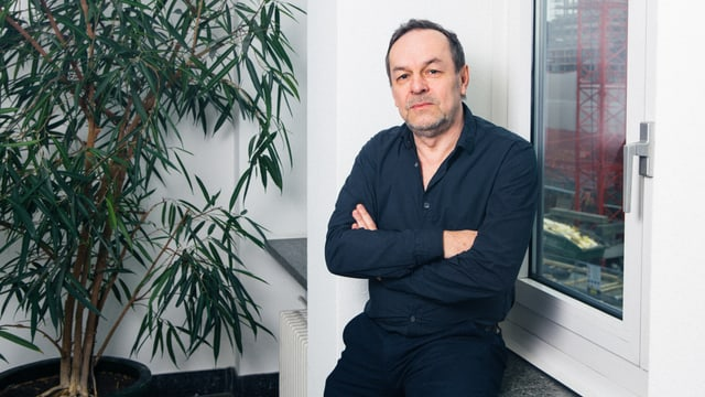 Ein Mann sitzt auf einer Fensterbank.