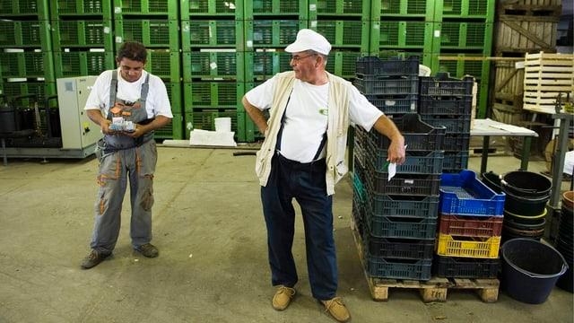 Zwei Arbeiter stehen herum.