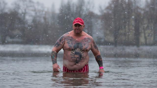 Ein Mann steht bis zur Hüfte im Orankesee im Winter