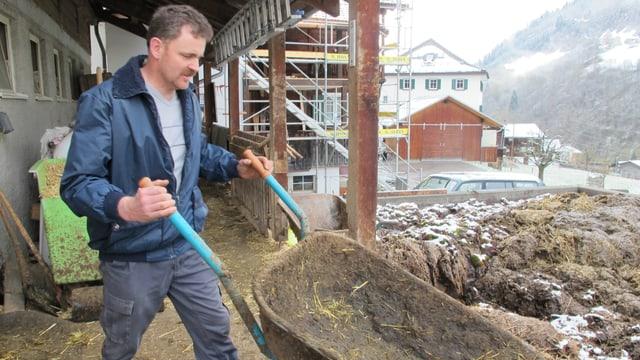 Ein Bauer kippt eine Schubkarre auf einen Misthaufen