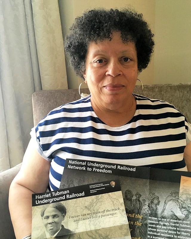 Eine Frau hält zwei Leaflets in die Kamera, die von der US-amerikanischen Sklavengeschichte berichten.