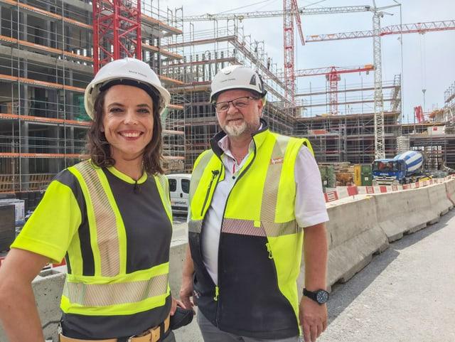 Mona Vetsch und Claudio Zanella stehen nebeneinander in Arbeitskleidung vor der Grossbaustelle