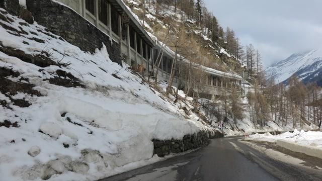 Eine schmale Strasse, oberhalb verläuft die Eisenbahnlinie.