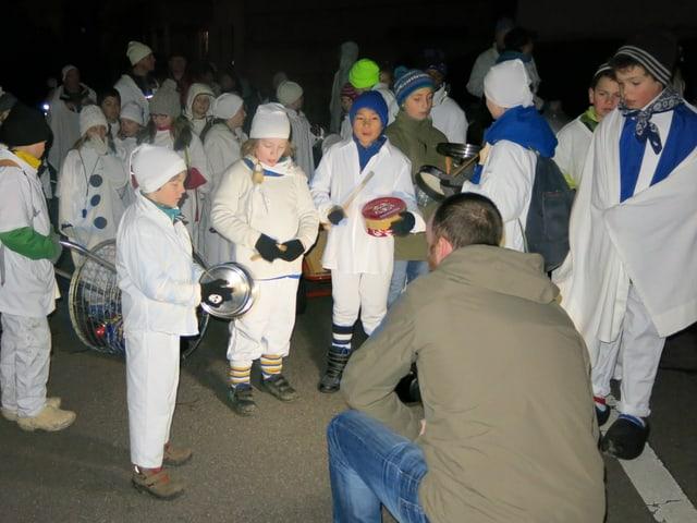 Weiss gekleidete Schüler stehen im Halbkreis und machen Lärm.