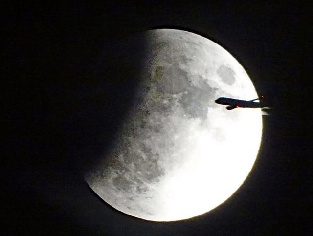 Flugzeug vor Mond.