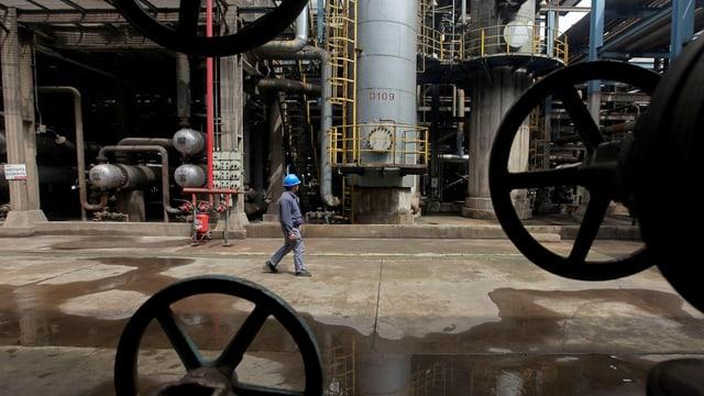 Arbeiter auf einem Raffineriegelände.