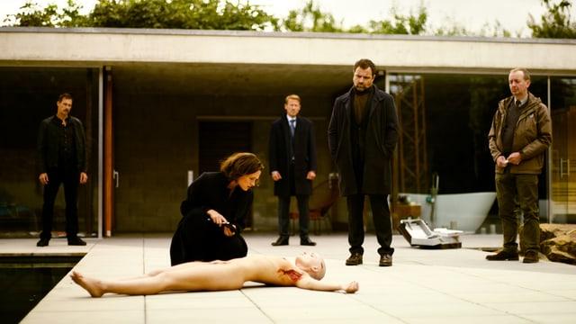 Vor einer Villa am Pool: Eine tote Frau liegt am Boden. Sie ist nackt, die Arme ausgestreckt, der Kopf rasiert, de Haut unter den Armen herausgeschnitten. Neben ihr kniet eine Frau und schaut auf die Leiche herunter. Im Hintergrund etwas weiter entfernt stehen vier Männer, die ebenfalls auf die Tote herunterschauen.