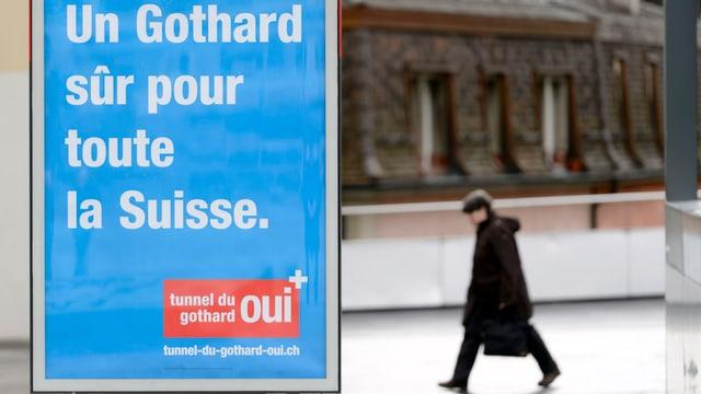 Eine Person geht hinten an einem Plakat für eine 2. Gotthardröhre (auf Französisch) vorbei.