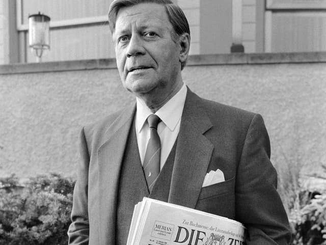 Schwarz-Weiss-Aufnahme von Helmut Schmidt mit einer Zeitung unter dem Arm.
