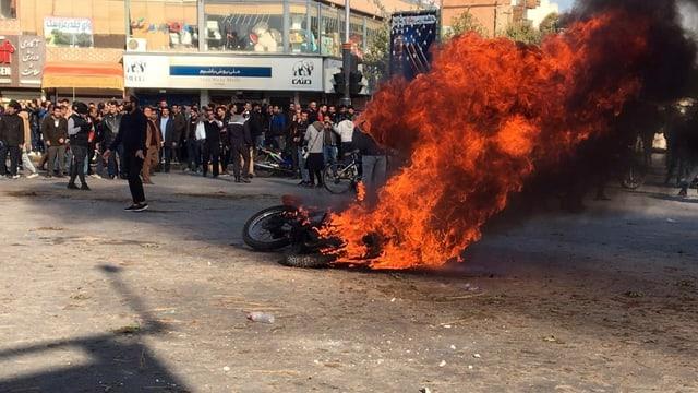 Brennendes Motorrad, dahinter eine Menschenmenge.