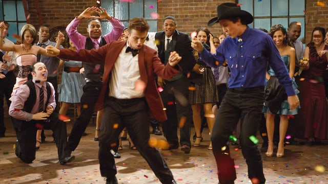 Zwei Männer tanzen im Vordergrund. Das Publikum im Hintergrund feuert sie an.