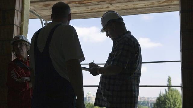 Kontrolleur befragt einen Bauarbeiter auf einer Baustelle
