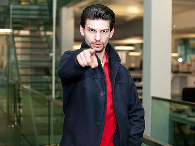 Baba Uslender in rotem T-Shirt und schwarzer Jacke, mit ausgestrecktem Zeigefinger.