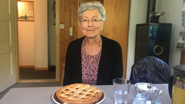 Portrait von Trudi Gartmann-Illien. Sitzt in ihrer Stube am Tisch. Vor ihr die Valser-Spezialität «Gätterlikuchen».