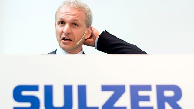 Ein Mann mit Mikrofon steht hinter einer Tafel mit der Aufschrift Sulzer.