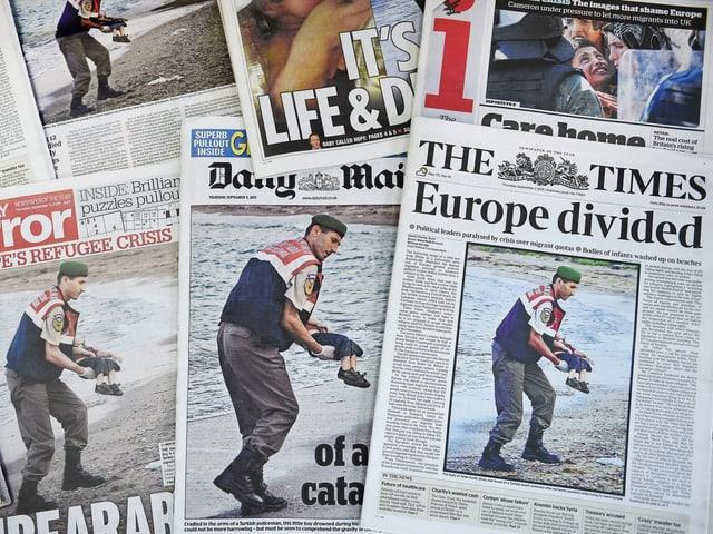 Ein Stapel an Tageszeitungen aus aller Welt, die das Bild des toten Junge auf der Frontseite haben.